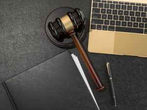 Wooden judges gavel and laptop computer on black leather desk
