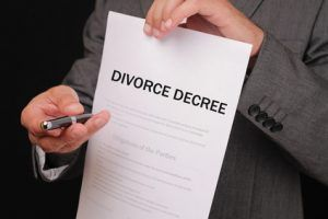 Divorce  concept. Man offering a pen to sign divorce decree close up.