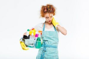 Exhausted woman holding cleaning supplies and having neck pain